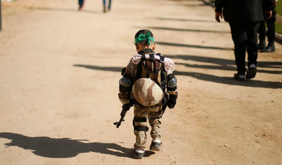 A Palestinian boy wearing a military costume arrives at a military-style graduation ceremony for Palestinian youths who were trained at one of the Hamas-run Liberation Camps, in Gaza City